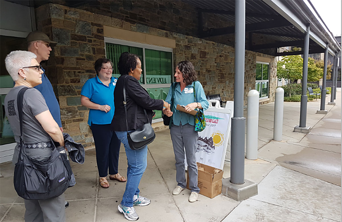 Tour leader Clare Lise Kelly (right) of the Montgomery County Planning Department greets Tina Patterson, the newest Planning Board member, who joined the group on the bus.