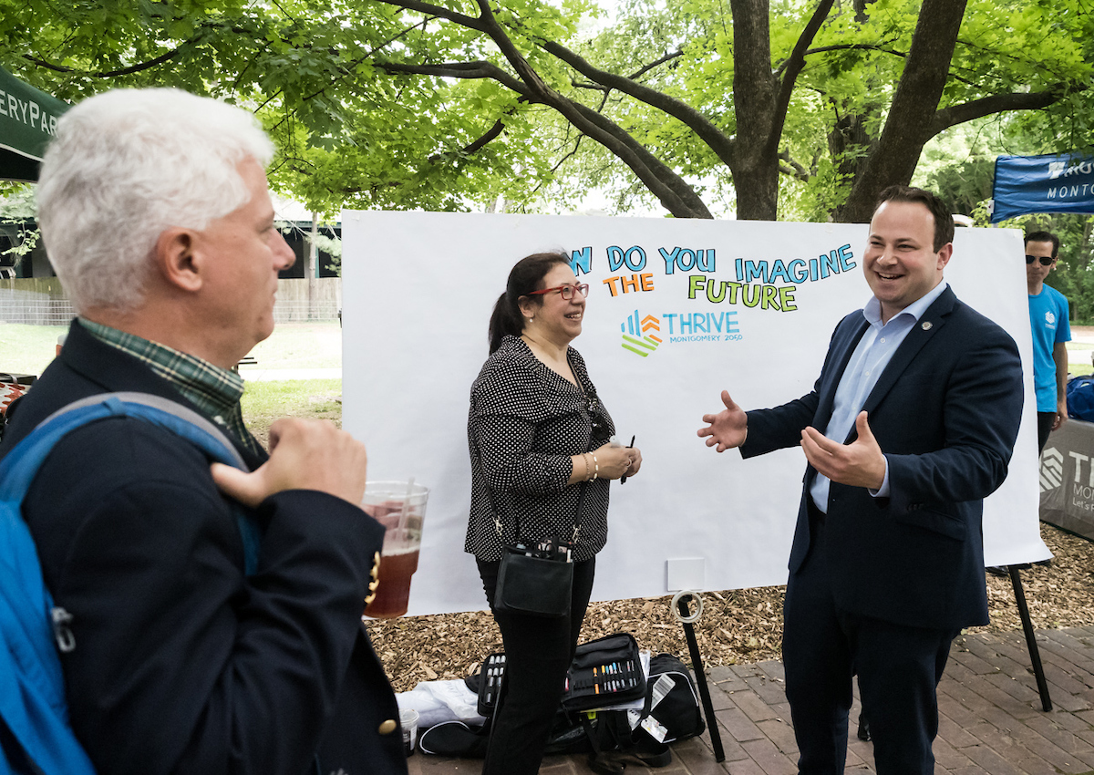 Planning Board Chair Casey Anderson and Montgomery County Councilman Andrew Friedson talk with graphic recording artist at Yappy Hour