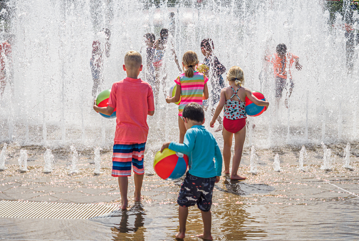 Children with beachballs playing in fountain