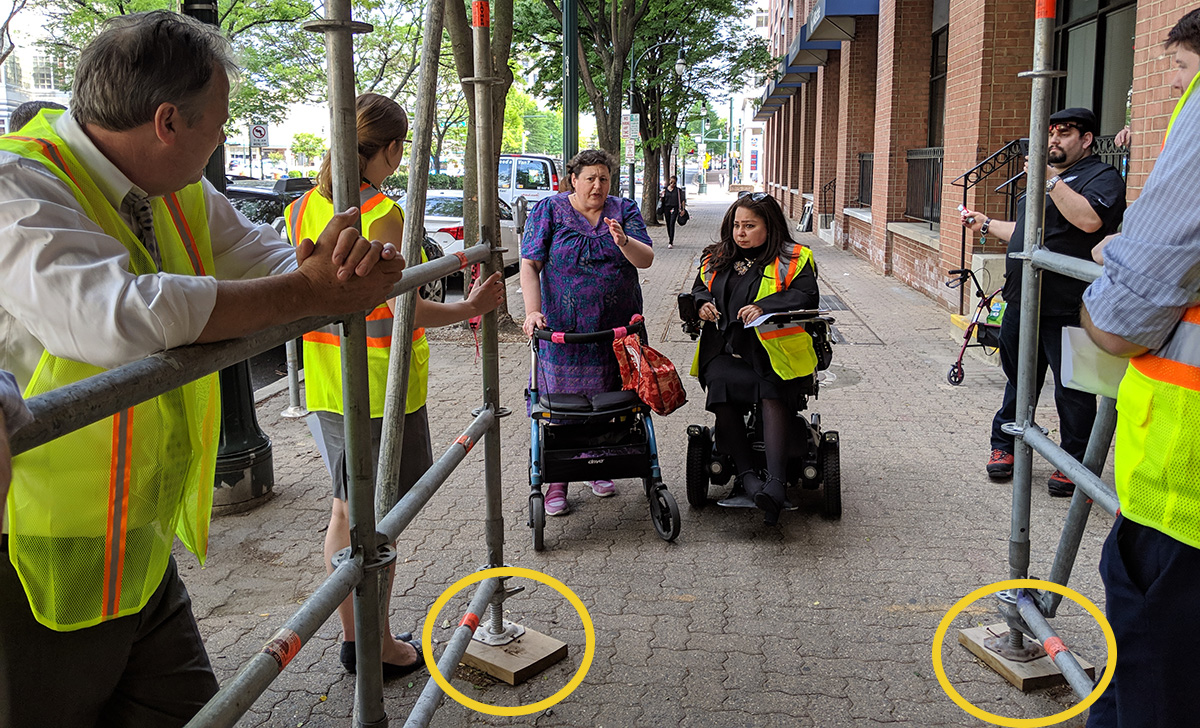 The scaffolding protecting the walkway barely accommodates two people using walking assistance devices. In fact, the circled supports narrow the walkway even further.