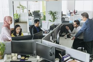Busy office with men and women working at desks