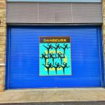 Adding simple color and graphic signage to an alley garage door heightens the character of place, even when it is behind the building.