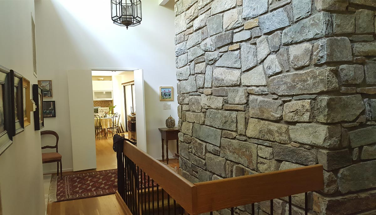 Clerestory windows bring bright light into the front foyer. A central chimney of locally quarried Stoneyhurst stone anchors the stairwell to lower level.