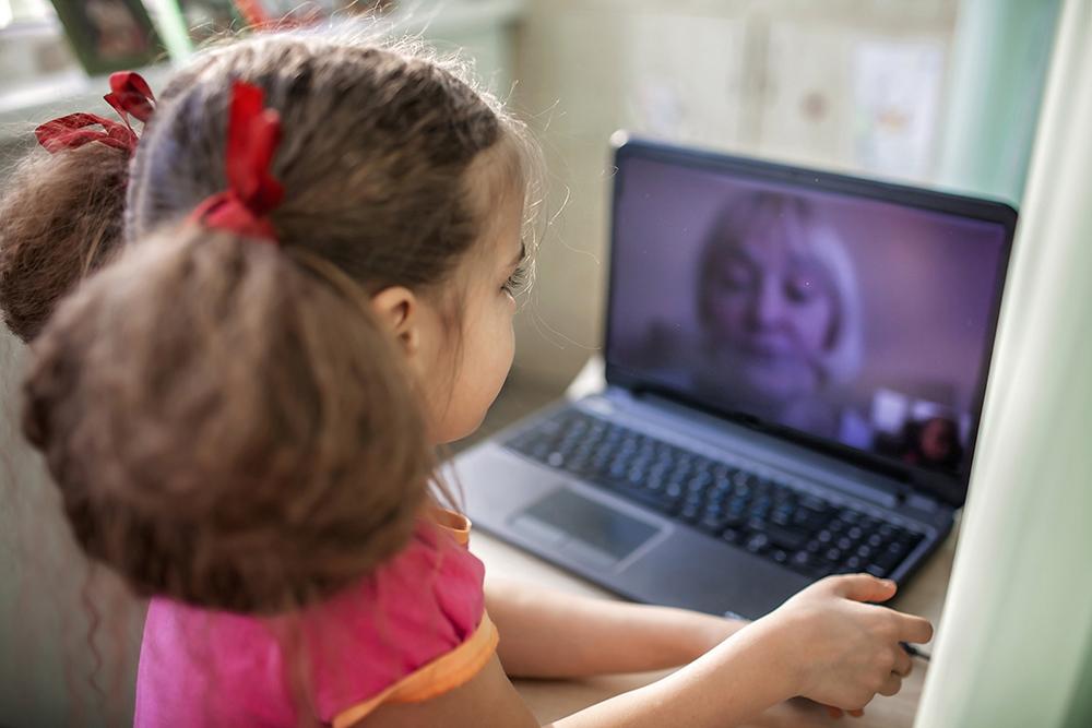 Cute girl talking with her grandmother within video chat on laptop, digital conversation, life in quarantine time, self-isolation