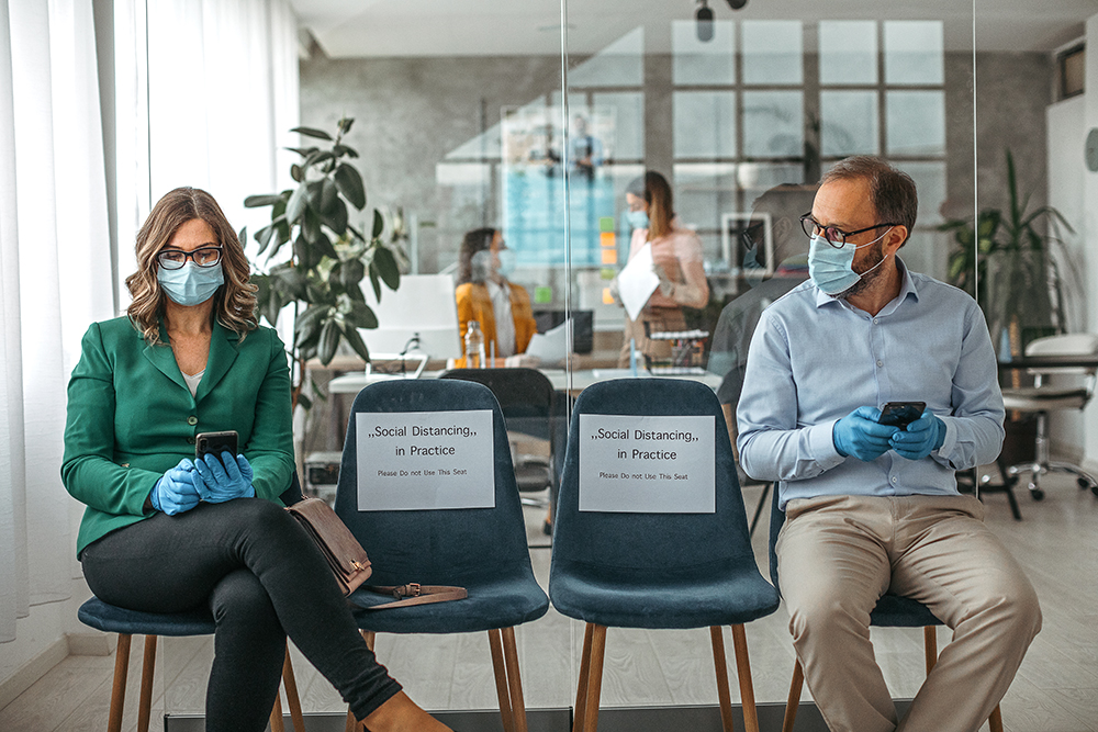 Customers using mobile phone wearing protective masks and gloves sitting on office chair while maintaining social distance to protect from COVID-19