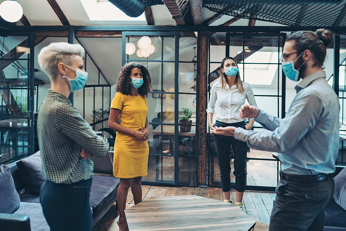 Three women and a man wear masks while standing and talking in an office space.