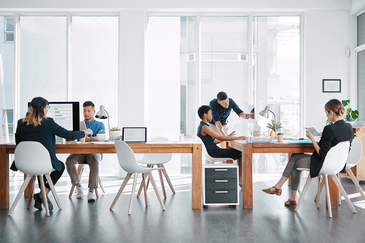 Modern open office with employees sitting at desks close to each other