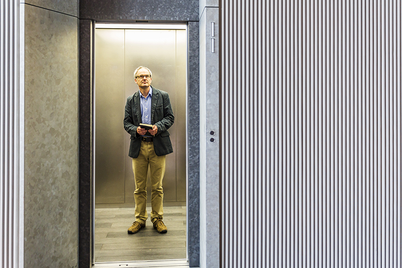 An older man standing alone on an elevator
