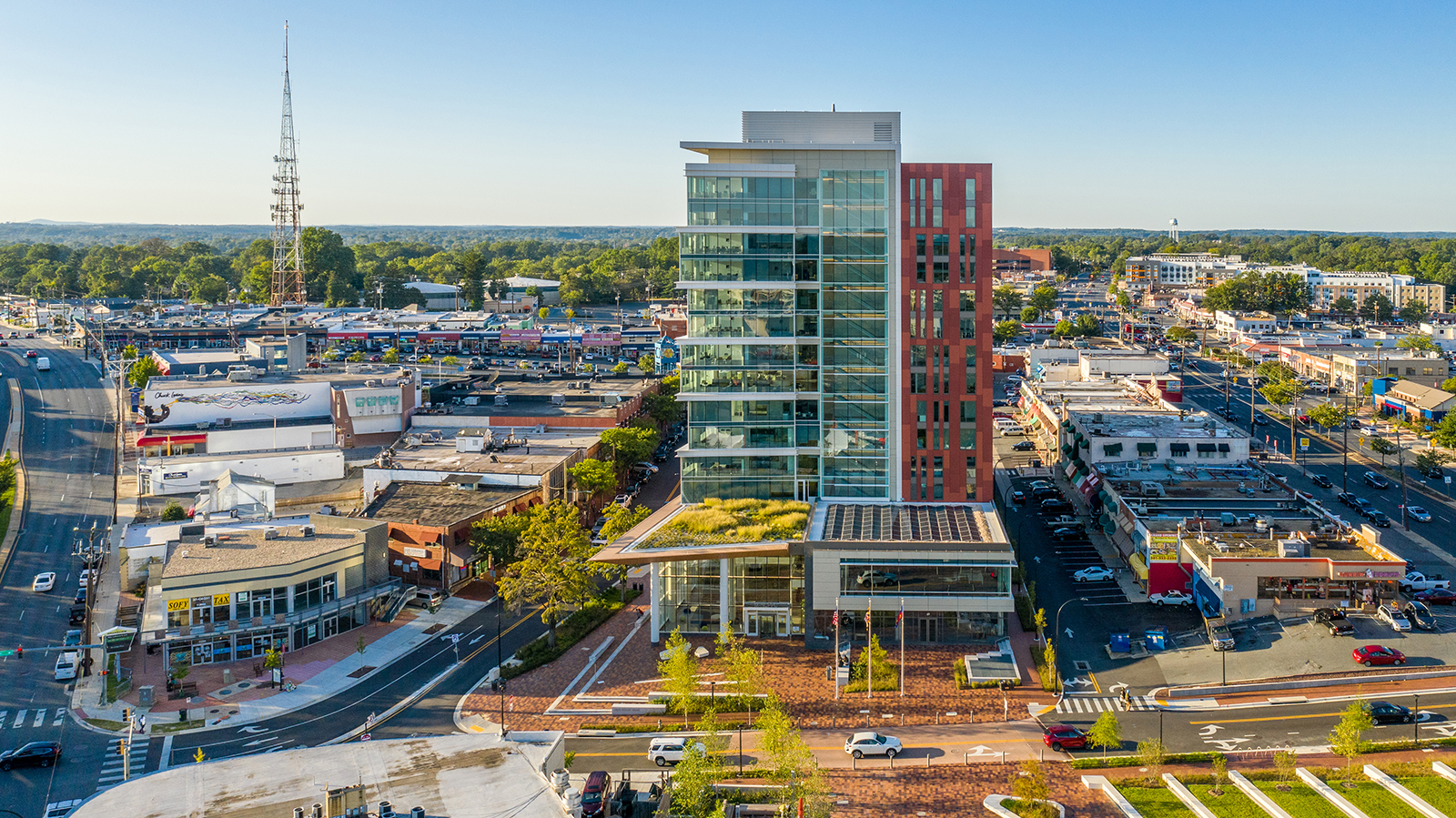 Aerial view of the south elevation and the entry plaza of the new Headquarters building with a green planted roof above the entry to the building, lots of glass and a brick red rain screen.