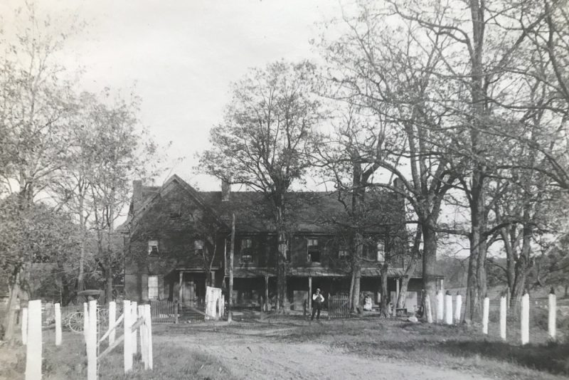 This photograph shows the Poor Farm almshouse circa 1910. It is a large frame structure with dark wood siding surrounded by large bare trees