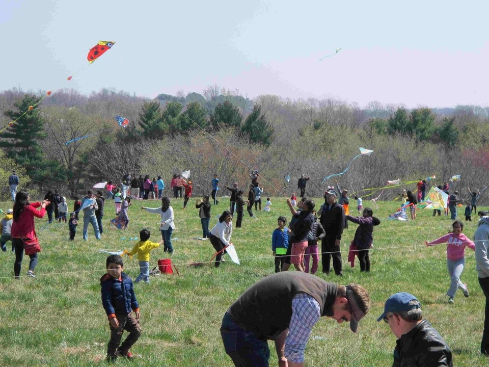 Many kids and families flying kites on a windy day at Ovid Hazen Wells Recreation Park during Montgomery Parks' Kites Over Clarksburg annual event.