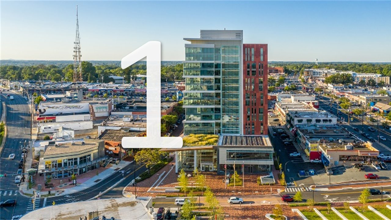 an aerial shot of the M-NCPPC Headquarters towering over the urban area of downtown Wheaton with a number one in front of the picture.