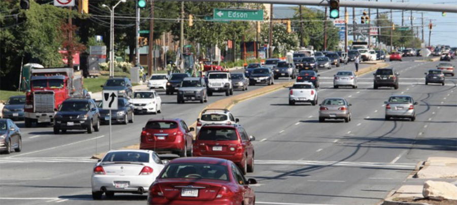 Wisconsin Avenue heading north towards North Bethesda. It shows six lanes of traffic with many cars heading north and south with retail in the distance