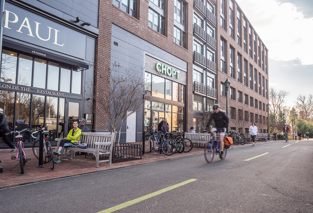 A man is shown riding a bicycle down the Bethesda Capital Crescent Trail in front of a mixed-use property. The downtown Bethesda apartment building has two fast-casual restaurants, Paul and Chop't, located on its ground floor.