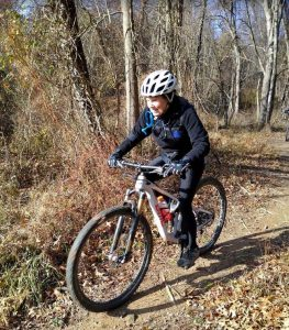 a female senior citizen riding on a mountain bike in a wooded area with a helmet
