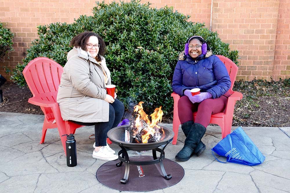 two women in winter coats sitting around a fire pit as part of Montgomery Parks' Picnic in the Park Warm Up Days at Acorn Urban Park. Participants could rent patio heaters and firepits in January 2021 as part of the program