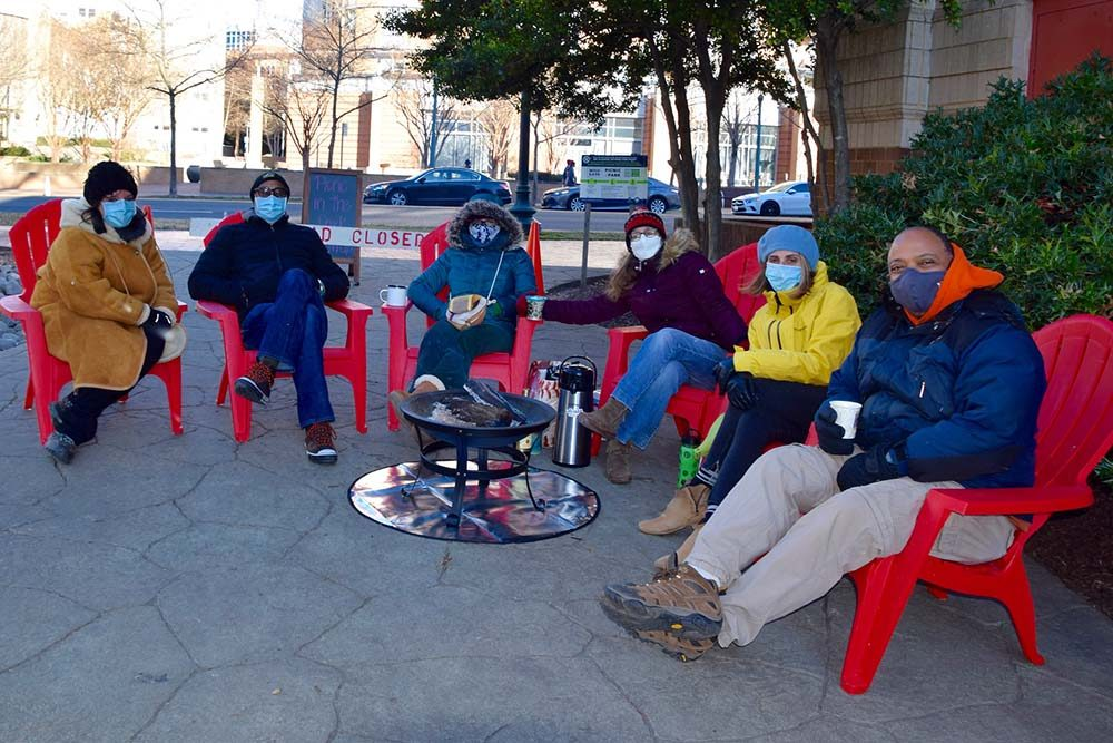 six people in winter coats sitting around a fire pit as part of Montgomery Parks' Picnic in the Park Warm Up Days at Acorn Urban Park. Participants could rent patio heaters and firepits in January 2021 as part of the program
