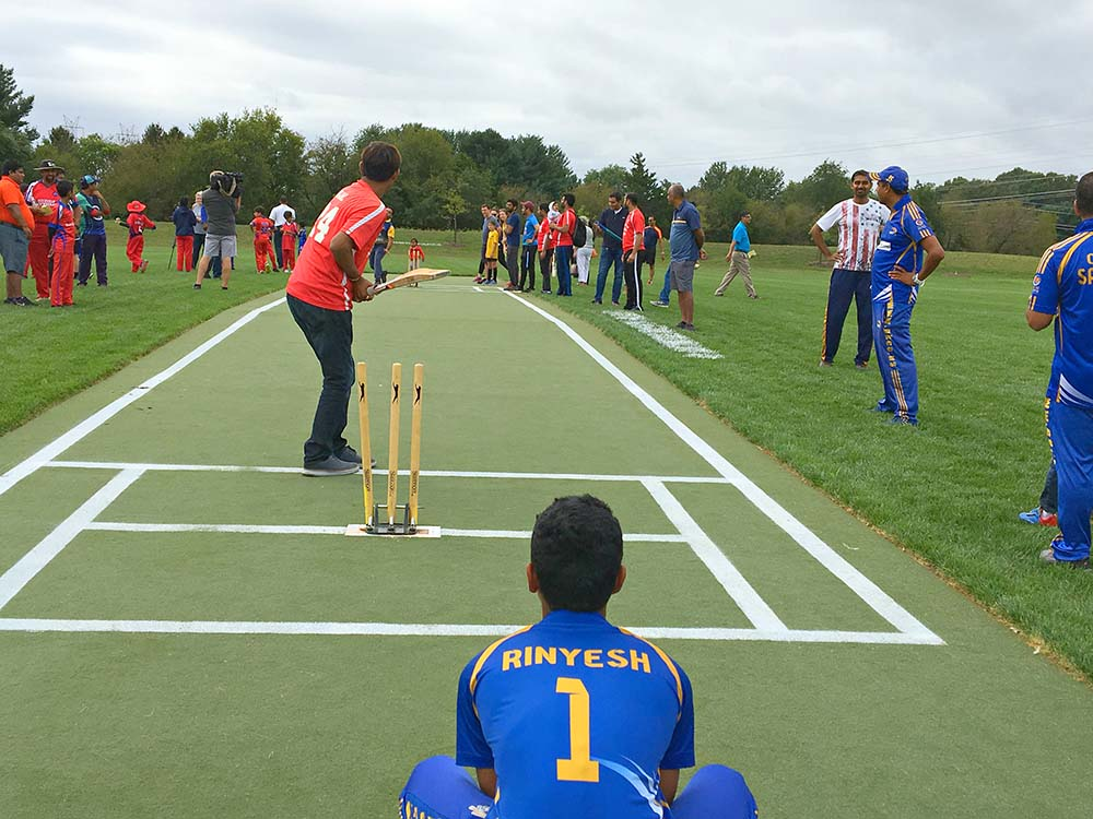 photo of the opening of the Montgomery Parks cricket field at South Germantown Recreational Park. Shows a cricket player on a field with players watching