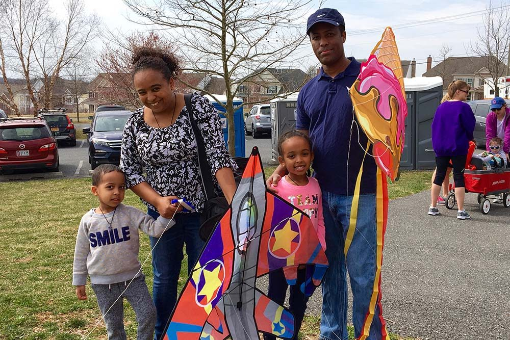 a family with a mother, father and two young children with two kites as part of Kites Over Clarksburg