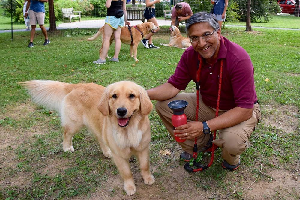 of a dog and owner looking happily at the camera with dogs and owners in the background of the photo at a Montgomery Parks Yappy Hour event in Bethesda
