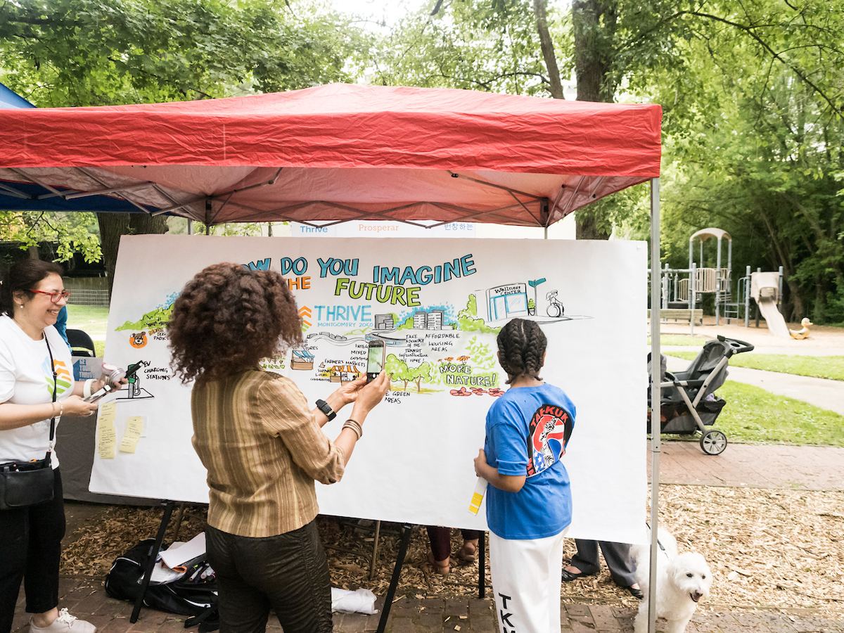 Artist talking with community members to create graphic recording