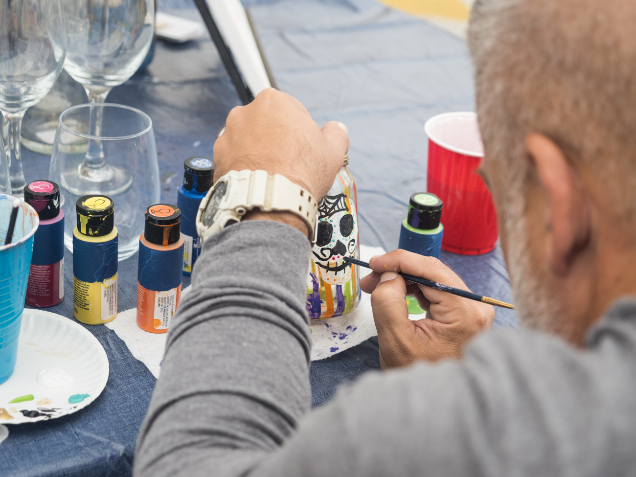 Man painting glass jar at Burtonsville Placemaking Festival