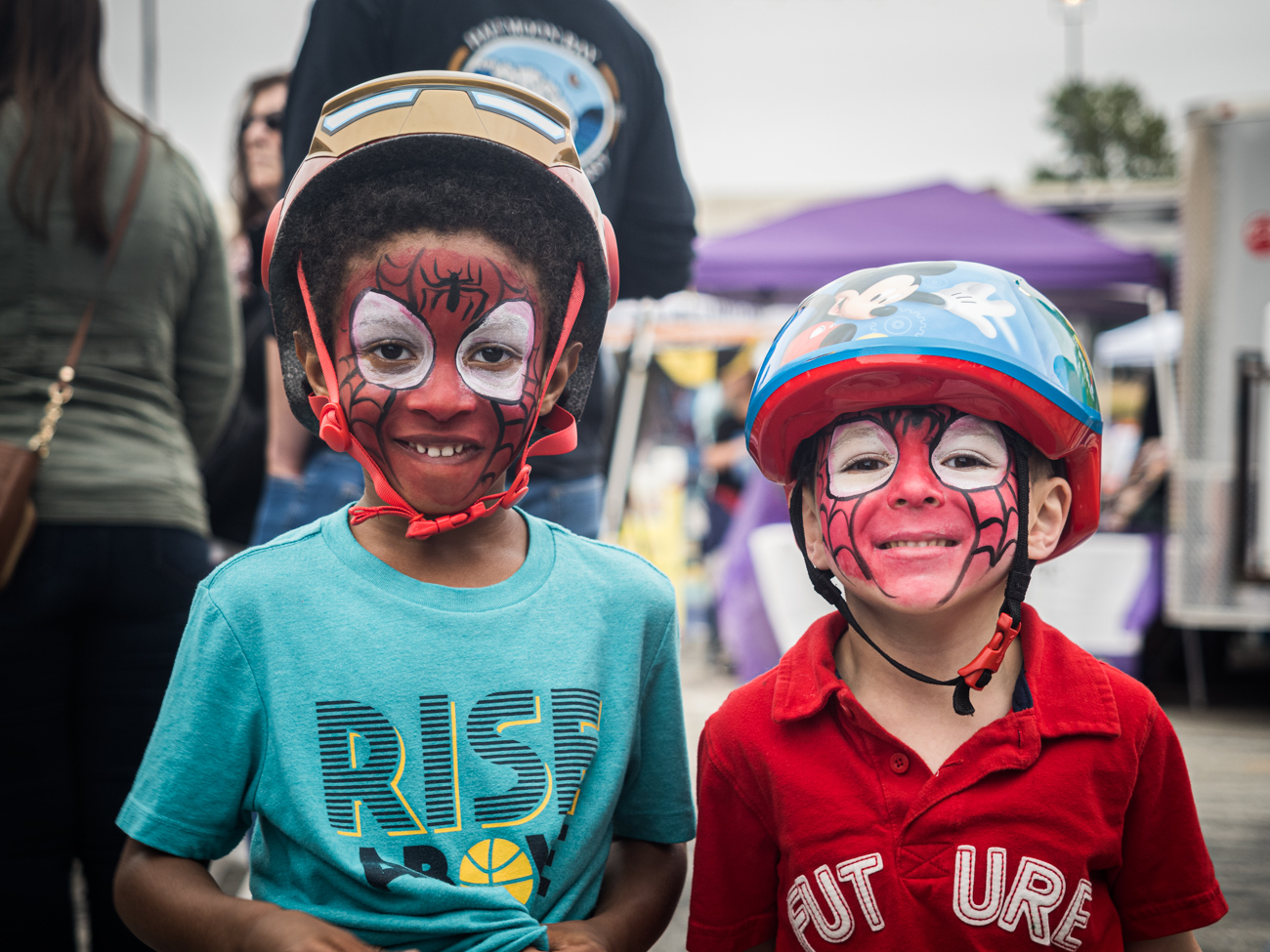 Two children with painted faces wearing bike helmets at Martial arts demonstration at Burtonsville Placemaking Festival