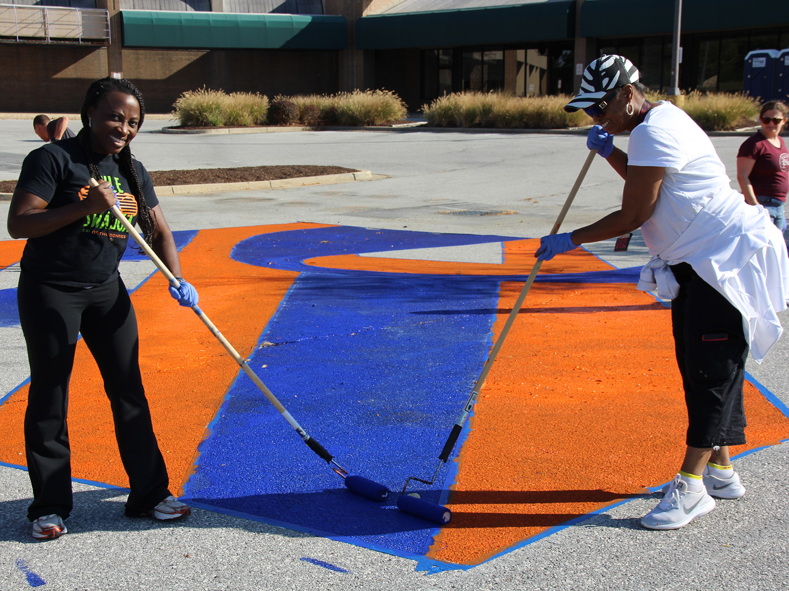 Volunteers paint parking lot to prep for Burtonsville Placemaking Festival