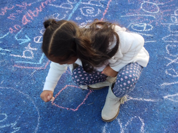 Child drawing with chalk on pavement at Burtonsville Placemaking Festival