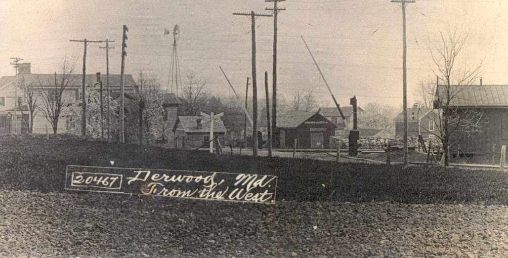 "monochrome historic photo: ""Derwood, MD from the west."" Railroad crossing and buildings."