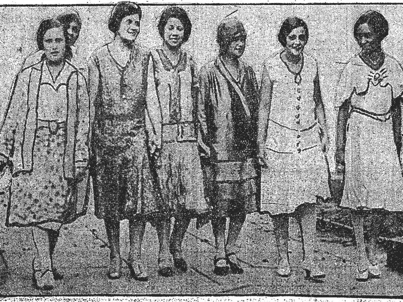 Seven women smile and walk towards the camera.