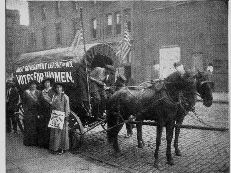 "Three women stand by a covered wagon with ""Just Government League of MD. Votes for Women"" painted on the side."
