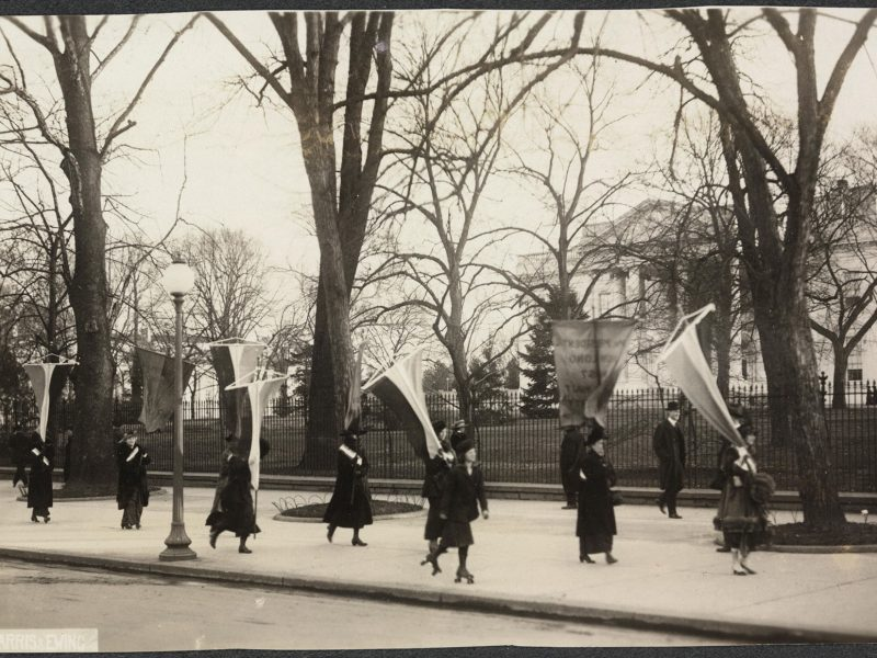 Women walk past the Whie House holding pro-suffrage flags and banners. One woman passes on roller skates.