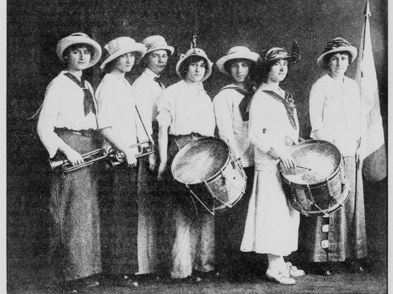 Seven women dressed in white carry drums, horns, and a flag.