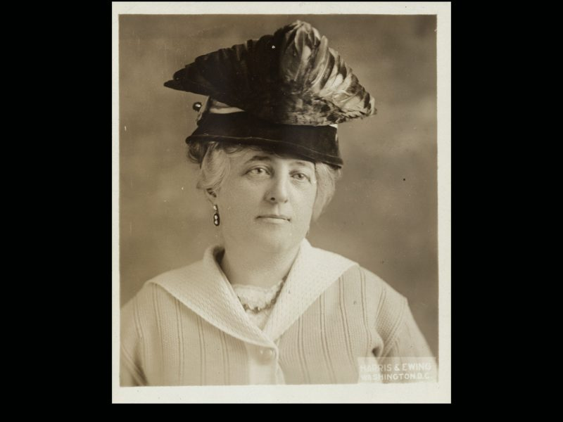 A professional portrait of a woman in a feather-trimmed hat.