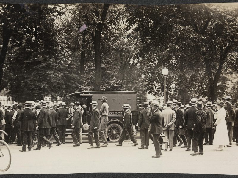 A crowd of mostly men looks on while a police car pulls up outside the White House.