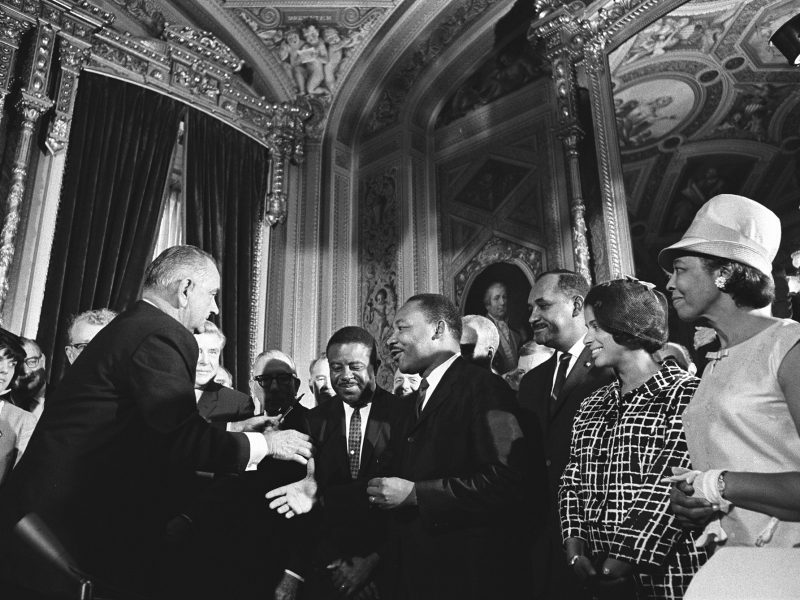President Lyndon B. Johnson moves to shake hands with Martin Luther King, Jr. as others look on