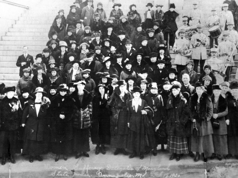 A large group of suffrage supporters, accompanied by a brass band, stand on the steps of the Maryland State House