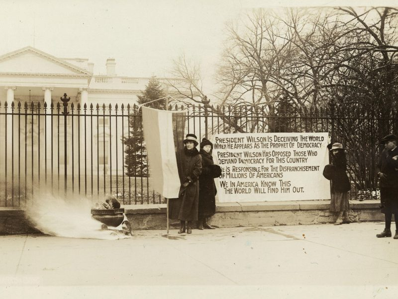 "Women hold a banner stating that ""President Wilson is deceiving the world,"" while a fire burns in an urn outside the White House."