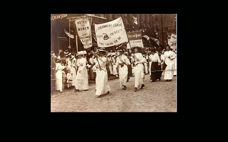 Women from the Just Government League marching and carrying suffrage banners.