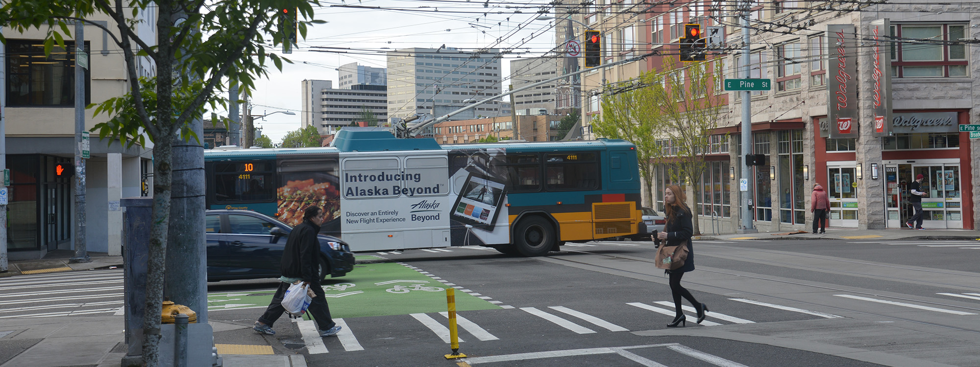 pedestrians in crosswalk, bus passing behind them