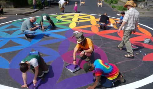 Group painting colorful design on street