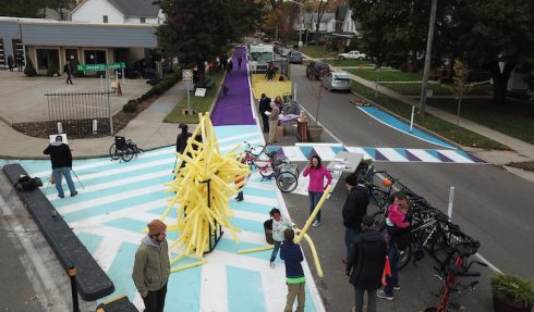 aerial view: children aly with foam noodles on street painted purple, light blue and white