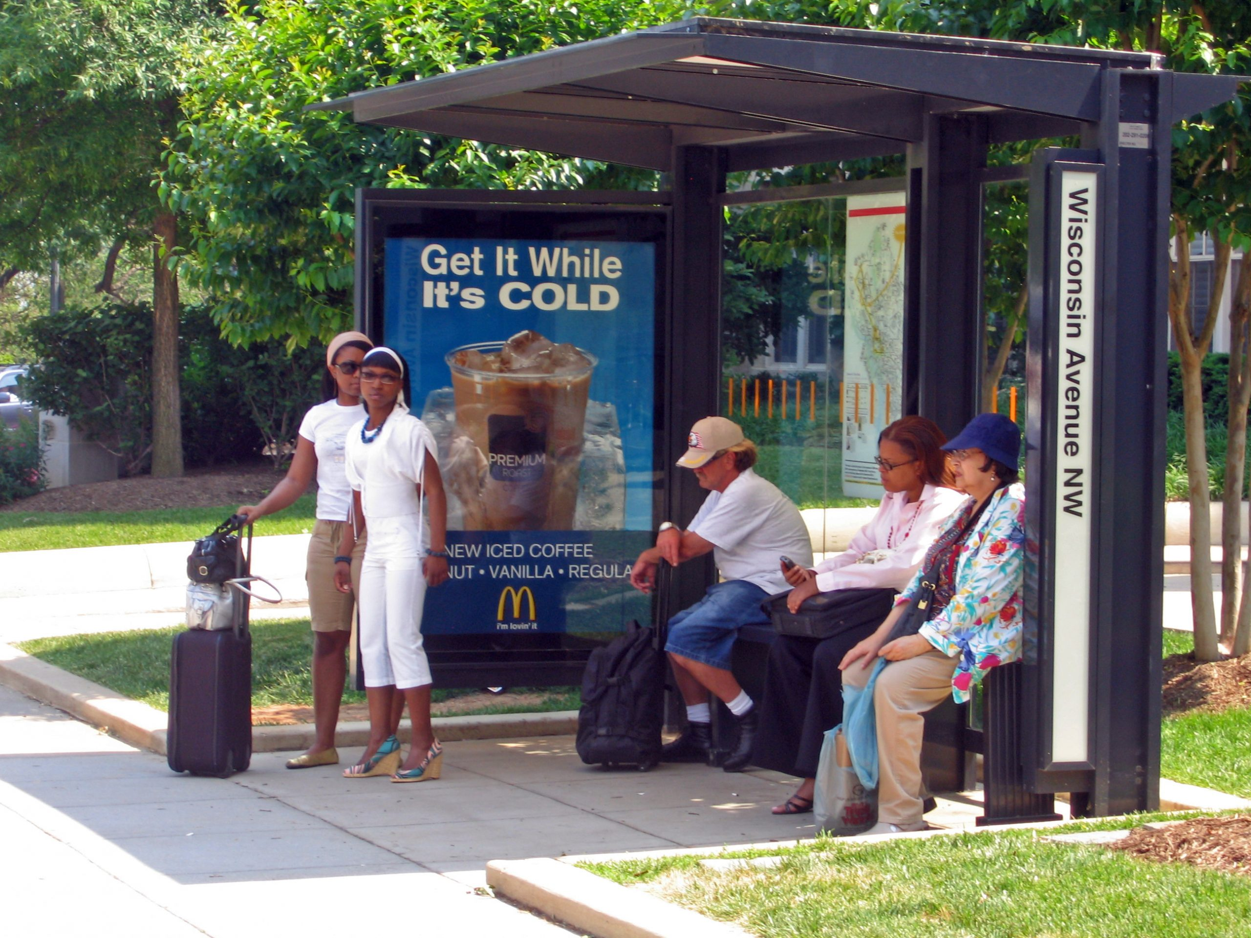 people at a bus shelter
