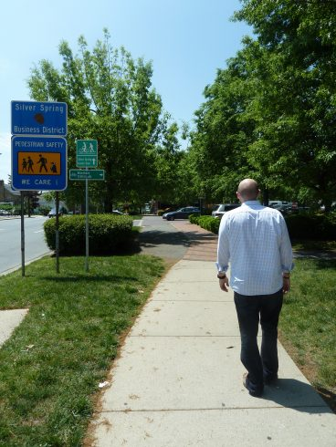 Man walking down a path that has wayfinding signage directing bicyclists and pedestrians.
