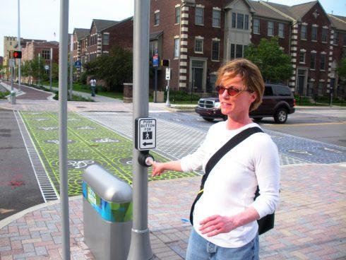 person pressing a walk button