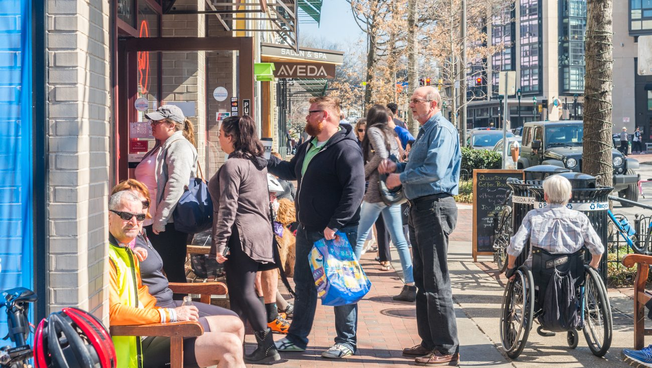 Pedestrians queue outside a business in downtown Bethesda.