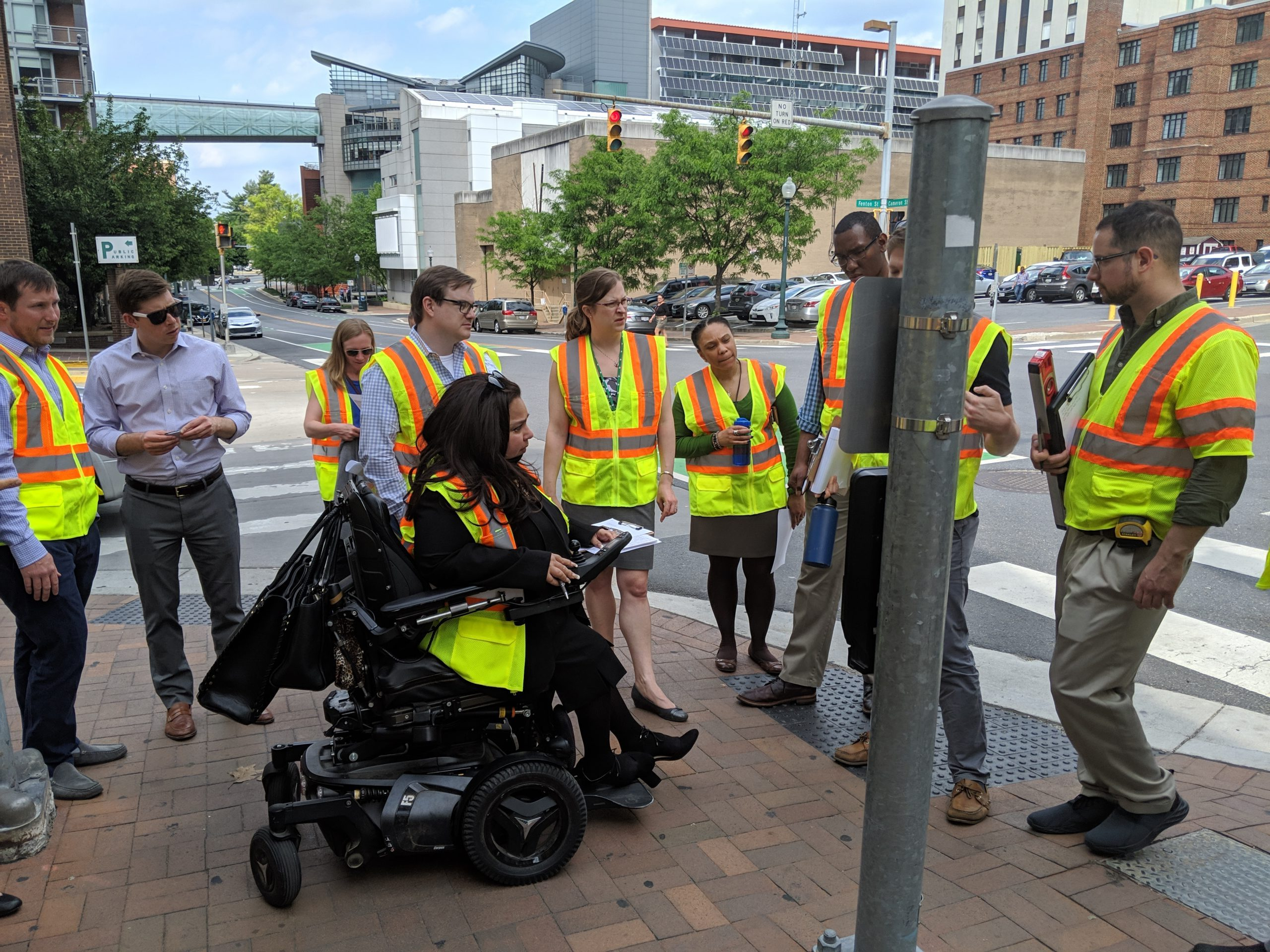 Pedestrian audit attendees in Silver Spring inspect an Accessible Pedestrian Signal while wearing reflective vests.