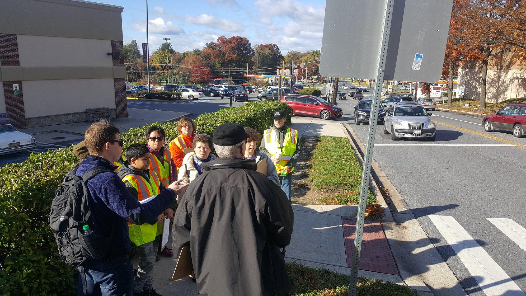 Pedestrian audit participants discuss a curb ramp and crossing in Aspen Hill.